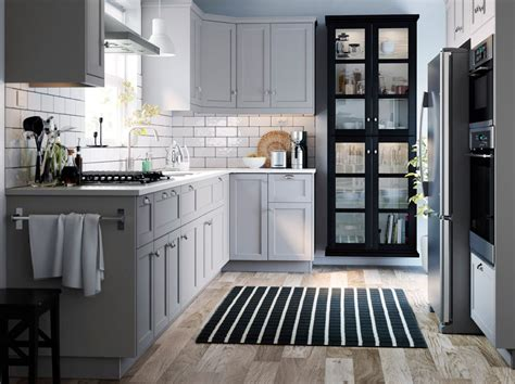 A small grey and white, traditional style kitchen with